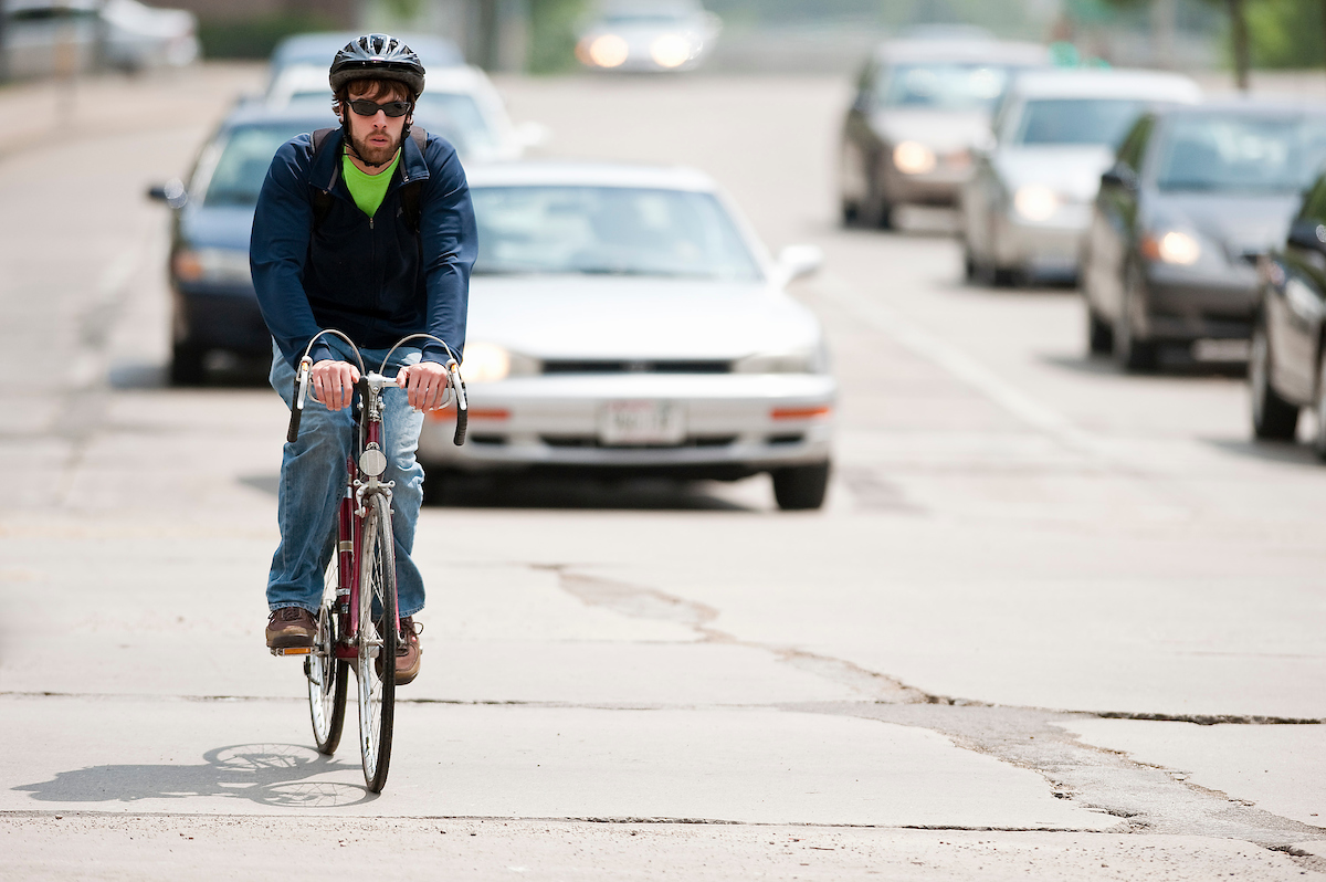 Man with a helmet is riding a bike along a road. Two cars are slightly behind him.