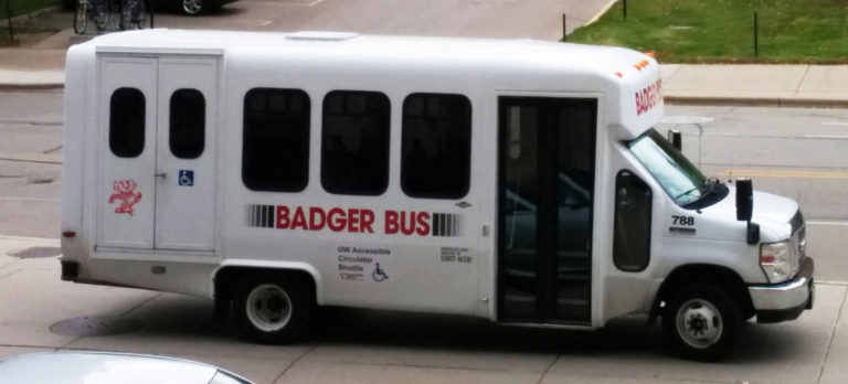 "Example image of what the accessible circulator shuttle may look like. A small white bus with ""Badger Bus"" written on the side. A sign on the side reads ""UW Accessible Circulator Shuttle."""