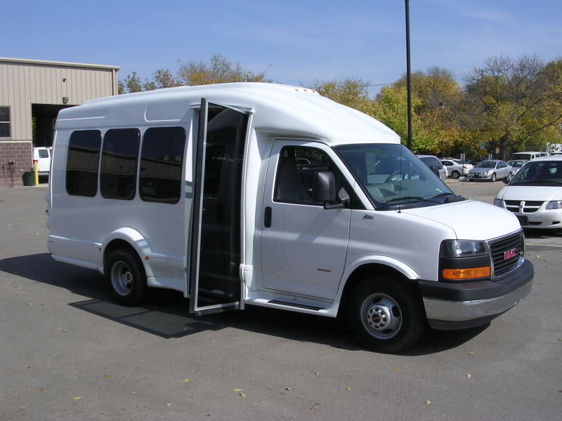 Image of the left side of the white bus, shot from the front. Loading door is open and UW decals are visible.