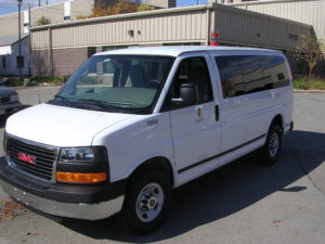Image of the white fleet passenger van's left side, shot from the front.
