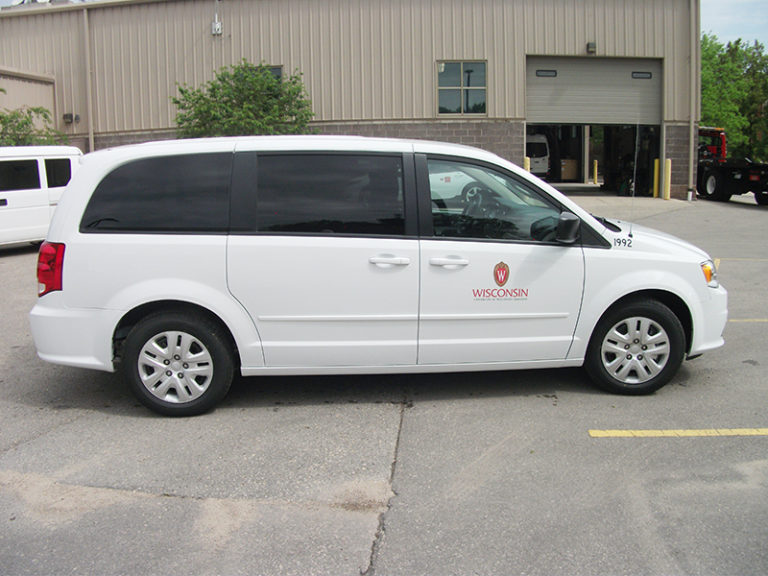 Side shot of a white minivan with UW decals.