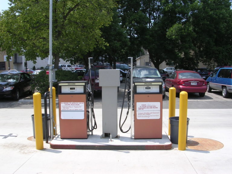 Close-up image of two gas pumps in the middle of a parking lot.