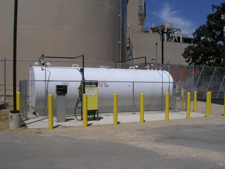 Close up shot of a large diesel fuel cylinder surrounded by yellow parking barriers.