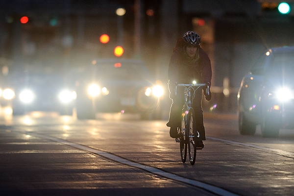 A helmeted bicyclists rides in a protected bike lane in the early evening, with the bike's front light bright. A row of cars, headlights on, are off to the right side.