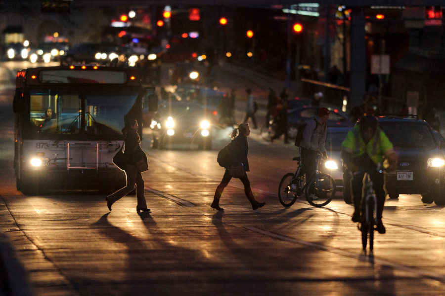 Pedestrians walk across an intersection along University Avenue against a backdrop of car lights and rush-hour traffic traveling through the heart of the University of Wisconsin-Madison campus at nightfall on Nov. 14, 2012. In the background at left is a Madison Metro bus.