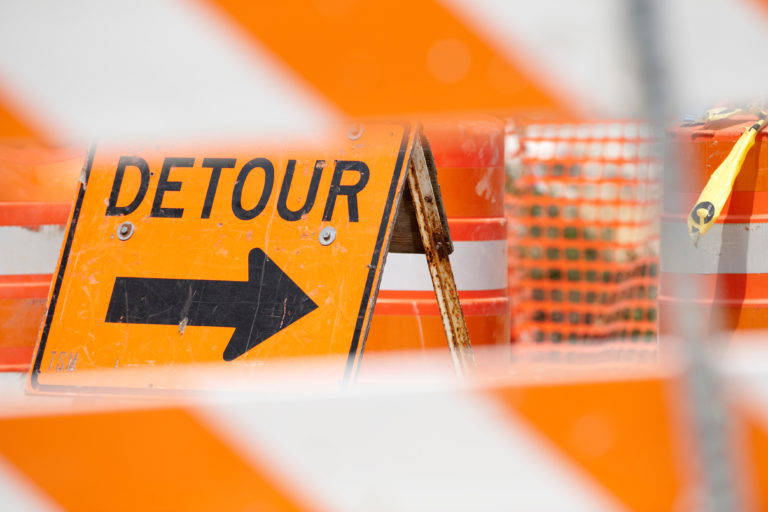 """Picture of an area blocked by construction barricades and other traffic management signs. Focus is on a bright orange sign stating """"Detour"""" with an arrow pointing to the right."""