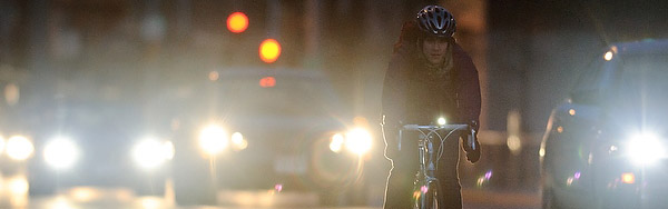 A bicyclist pedals in the bike lane along University Avenue against a backdrop of car lights and rush hour-traffic traveling through the heart of the University of Wisconsin-Madison campus at nightfall on Nov. 14, 2012.