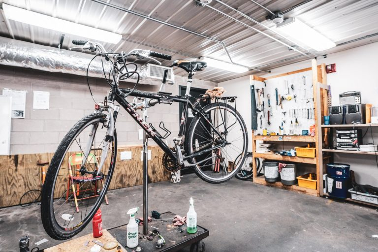 A black bicycle is elevated on a stand so it can be worked on. Interior of the University Bicycle Resource center is visible; a tool bench can be seen in the background.