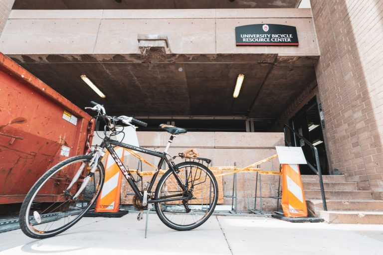 An image shot from below of a black bicycle displayed in front of the lower level of Lot 6, where a sign for the University Bicycle Resource Center is visible in the background.