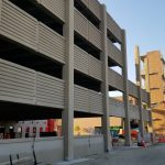 View from the ground of the side of the new partially constructed parking structure, lacking several panels and glass.