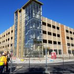 Wide shot of the nearly complete new parking facility. Glass has been installed on the stairwell column. Fencing surround the site and two construction workers in safety gear are seen on the left.