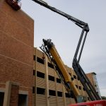 A tall, articulated lift crane is helping construct the side of the parking garage.