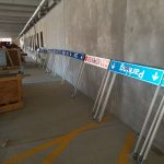 """A collection of yet-to-be-installed parking wayfinding signage, including a """"Parking to the right"""" and """"Do Not Enter"""" signs."""