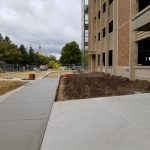Street level image showing fresh sidewalk running along side the under-construction new parking facility.