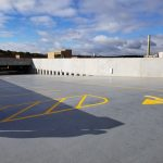 View looking down the ramp up to the rooftop level. Newly painted yellow signage and directional markers are visible on the pavement.