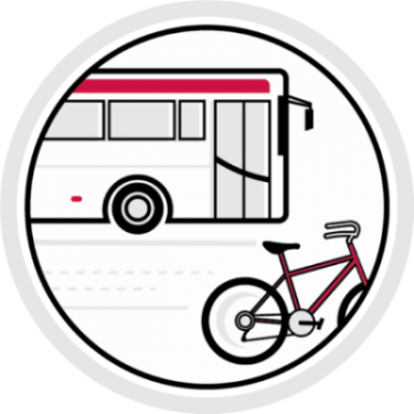Red and white colored circular transportation icon, includes a bus and bicycle near each other on the road.