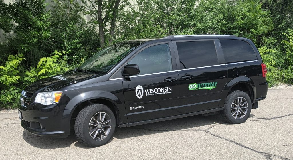 Image of the accessible circulator shuttle vehicle -- a black van with the UW-Madison logo in white and black and the vendor's logo on the vehicle's doors. UW logo can also been seen on the hood of the van. Van is equipped with a wheelchair lift.